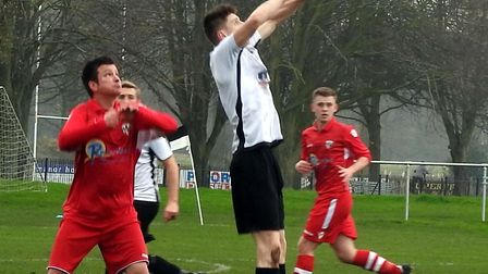 Beccles Town's hat-trick hero Rob Bishop stretched for a header Picture: David Walters