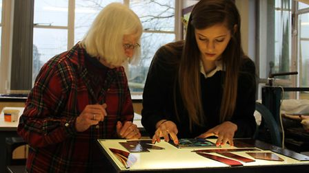 Glass artist Teri Lockton and a pupil at Hartismere School make part of the newly installed stained
