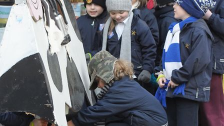 Children from the St Paul's Cathedral School try their hand at milking a cow