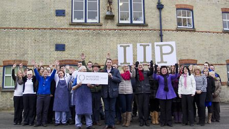 Adnams colleagues celebrate the firm's Gold Investors in People award outside the Southwold brewery