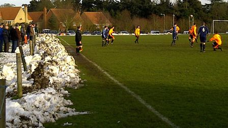 Snow is piled up beside the pitch as Coplestonians take on Wickham Market last Saturday