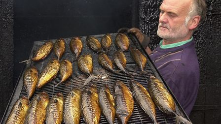 Steve Richardson removes a tray of fish from the oak smoke house, at Orford
