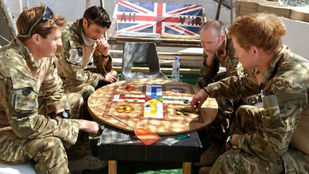 HRH Prince Harry plays a game of Uckers with fellow pilots at the British controlled flight-line in