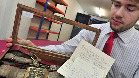 Auctioneer Timothy Medhurst of Reeman Dansie, Colchester with military dress belts belonging to Capt