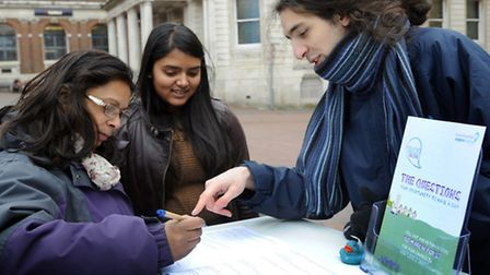 Kiran Sinha and her daughter Priya Sinha fill out a consultation form with the help of Oliver Garrat