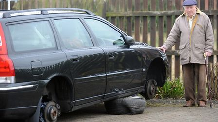 Stanley Watts is pictured beside his car in Bures after somebody stole the wheels.