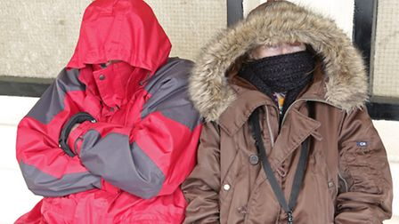 WARM INSIDE: Two people trying to keep warm in the bitterly cold winds that blew at Woodbridge Tide