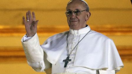 Pope Francis waves to the crowd from the central balcony of St. Peter's Basilica at the Vatican, Wed
