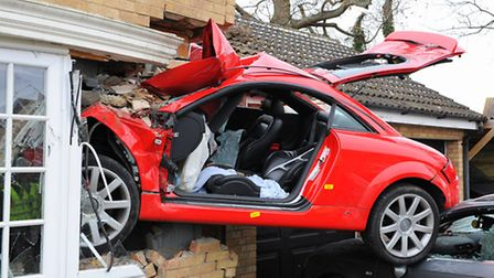 An Audi TT which left the road and crashed through a hedge, over two cars parked in a driveway and i