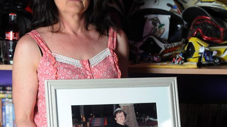 Joanne Louis holds a photo of her son Rhys Loram by what remains of his memorial in his younger brot