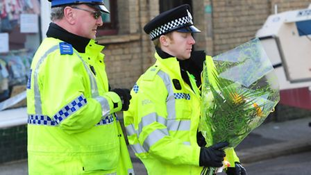 Policemen place the flowers at the house in Grosvenor Road, Lowestoft.