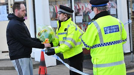 A man leaves flowers at the house in Grosvenor Road, Lowestoft.