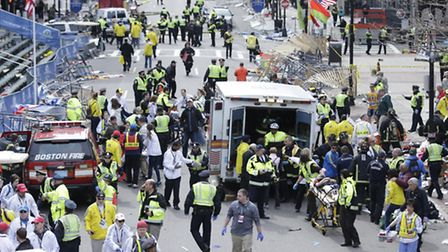 Medical workers aid injured people at the finish line of the 2013 Boston Marathon following an explo