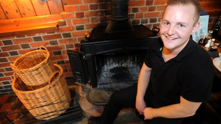 Bar manager Mark Cooper next to the fire at The Harbour Inn, Ferry Road, Southwold.