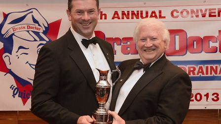 Rob Simpson, left, receives his marketing award from Drain Doctor Plumbing chairman Freddie Mitman