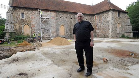 Father Bernard Rolls pictured on the foundations of the church extension earlier this year.