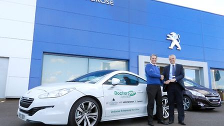 Golf professional Stuart Robertson receives the keys for his new RCZ from Gavin Oliver, sales manage