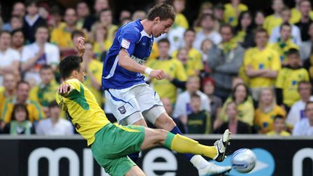 Connor Wickham of Ipswich Town (R) fires in a cross past Russell Martin of Norwich City back in a de