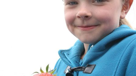 Mia Murray with one of the few ripe strawberries available at Tiptree Open Farm Day