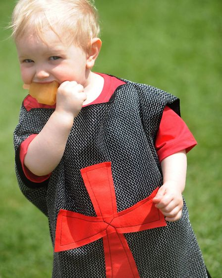 Harry Smith, one, eats an ice cream while dressed as a knight at the Framlingham Castle knights tour