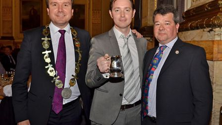 Fergus Fitzgerald, centre, head brewer at Adnams, receives his Brewer of the Year award from Simon J