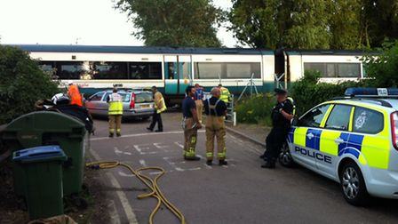 A train has collided with a car on a level crossing in Woodbridge