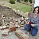 Karen Stacey holds a piece of the police car that smashed into her home on Downside Close in Ipswich