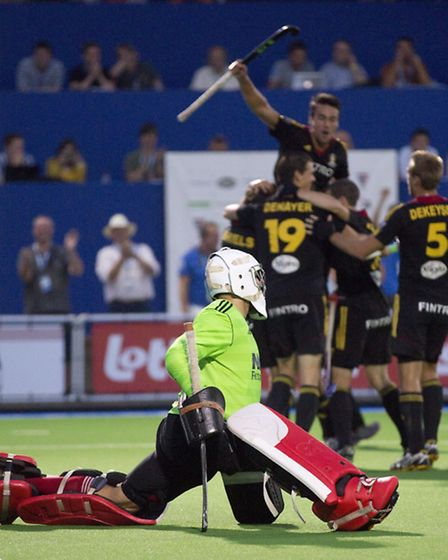 England's goalkeeper George Pinner looks on as Belgian team players jubilate after scoring during a