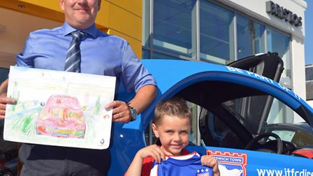 Ashton Taylor-Buglione receives a replica Ipswich Town shirt from Bristo's Renault sales manager Rob