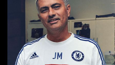 Jose Mourinho signing his football boots.