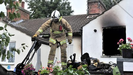 A firefighter examines the aftermath of a house fire