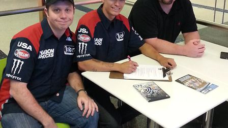 At LA Airport on Wednesday afternoon, Gino Manzares (centre) signs his Ipswich Witches contract with
