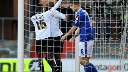 Jabo Ibehre is congratulated by Blair Turgott after scoring Colchester's second at Oldham on Saturda