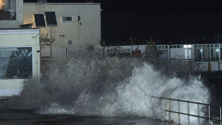 Waves batter the seafront near the pier in Southwold.