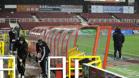 Swindon Town ground staff sweeping rainwater away from the dug-outs at The County Ground before the