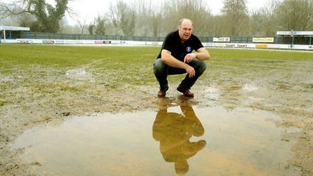 Bury Town chairman Russell Ward on a waterlogged Ram Meadow pitch