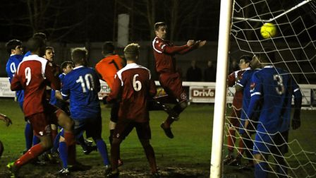 Craig Parker, right in red, leaps to score Bury's second at Ram Meadow last night. Photo: ANDY ABBOT