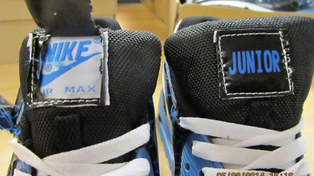 Fake Nike shoes found in cargo at the Port of Felixstowe, showing the Junior labels stitched over th