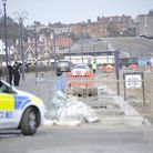 A black van carries away a body that washed up on a beach in Felixstowe