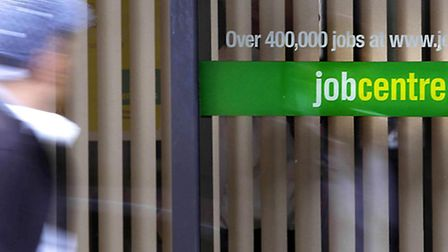 File photo dated 15/07/09 of a person passing a Job Centre Plus, as unemployment fell by 77,000 betw
