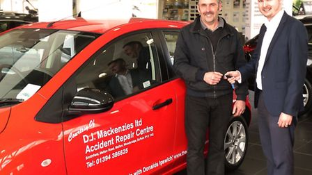 Neil Empson, left, owner of D J Mackenzies Accident Repair Centre, collects the Mazda2 superminis fr