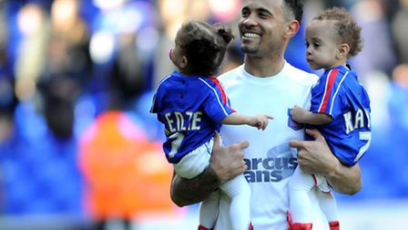 Carlos Edwards does a lap of honour with his young twins, who were born prematurely during his time
