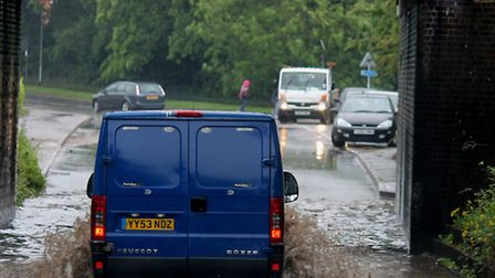 A van driving along a flooded road. File photo