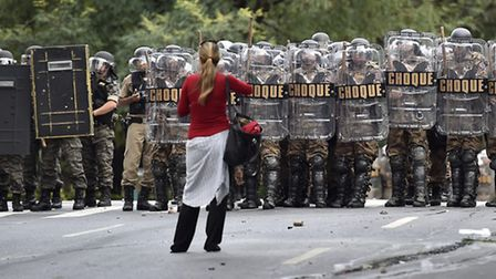A woman stands in front of a line of riot police during a violent demonstration during the 2014 socc