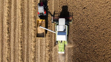 Aerial Shot of combine loading barley into trailer and also from the harvester itself