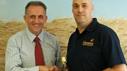 Dr Nigel Davies of Muntons presents a bottle of scotch and a cheque for �240 for the St Elizabeth Ho