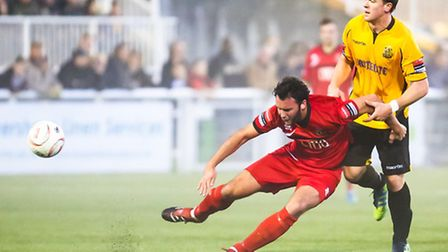 AFC Sudbury player James Baker tries to get a shot in as he is held back by Maidstone's Sonny Miles