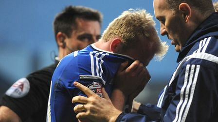 Jonny Williams leaves the field in agony, escorted by Ipswich Town physio Matt Byard, during the rec
