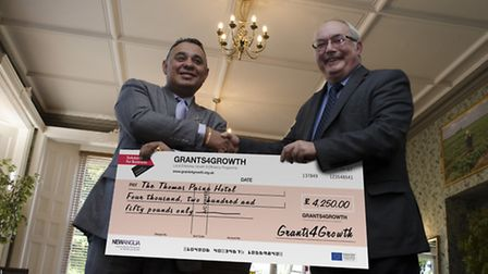 Chez Chetal, left, executive director at the Thomas Paine Hotel in Thetford, receives its grant cheq