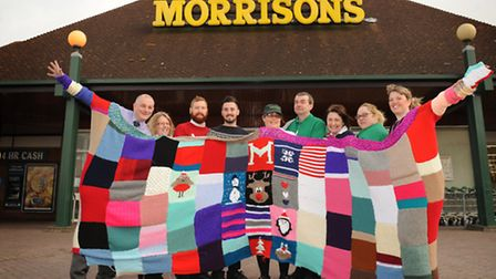Staff at Morrisons in Felixstowe have knitted a jumper big enough for 20 people. L-R Dale Robinson,